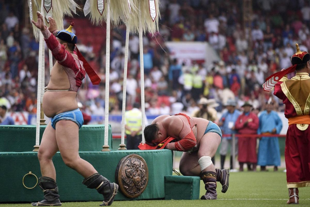 """Mongolian wrestler Enkhtuvshingiin Oyunbold celebrating his victory in front of the """"Nine White Banners"""" (the peacetime symbol of the Mongolian state) as the runner up (left) performs an eagle dance."""