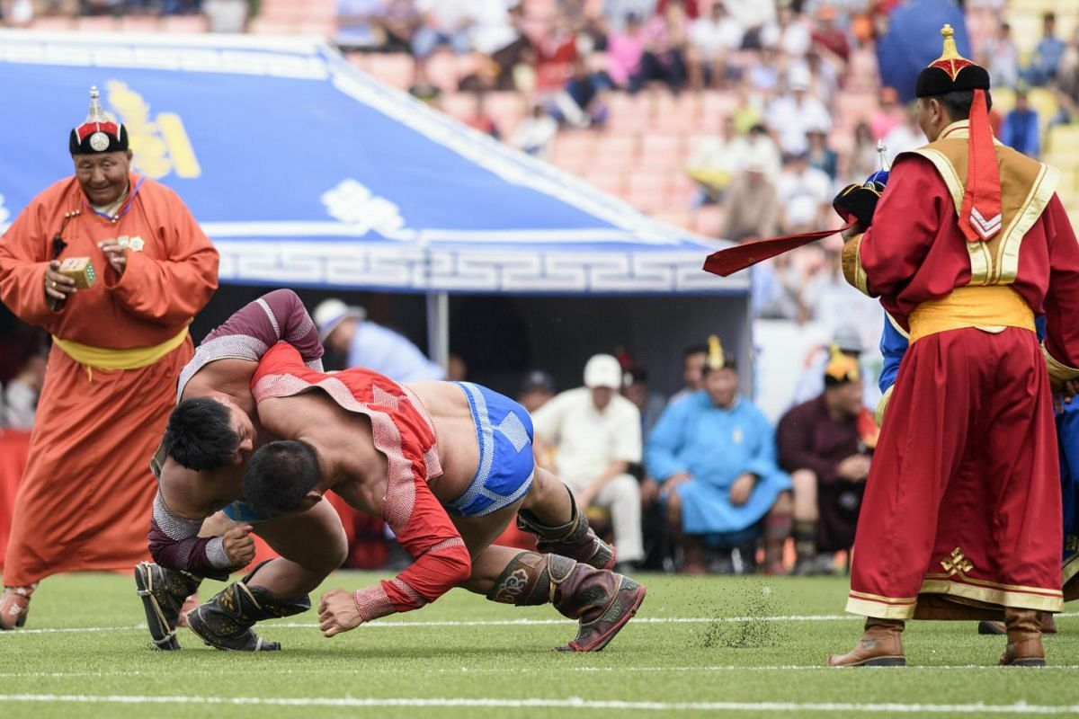 Mongolian wrestler Enkhtuvshingiin Oyunbold (2nd left) defeating an opponent in the seventh round during the National Naadam Festival at the Central Stadium in Ulan Bator.