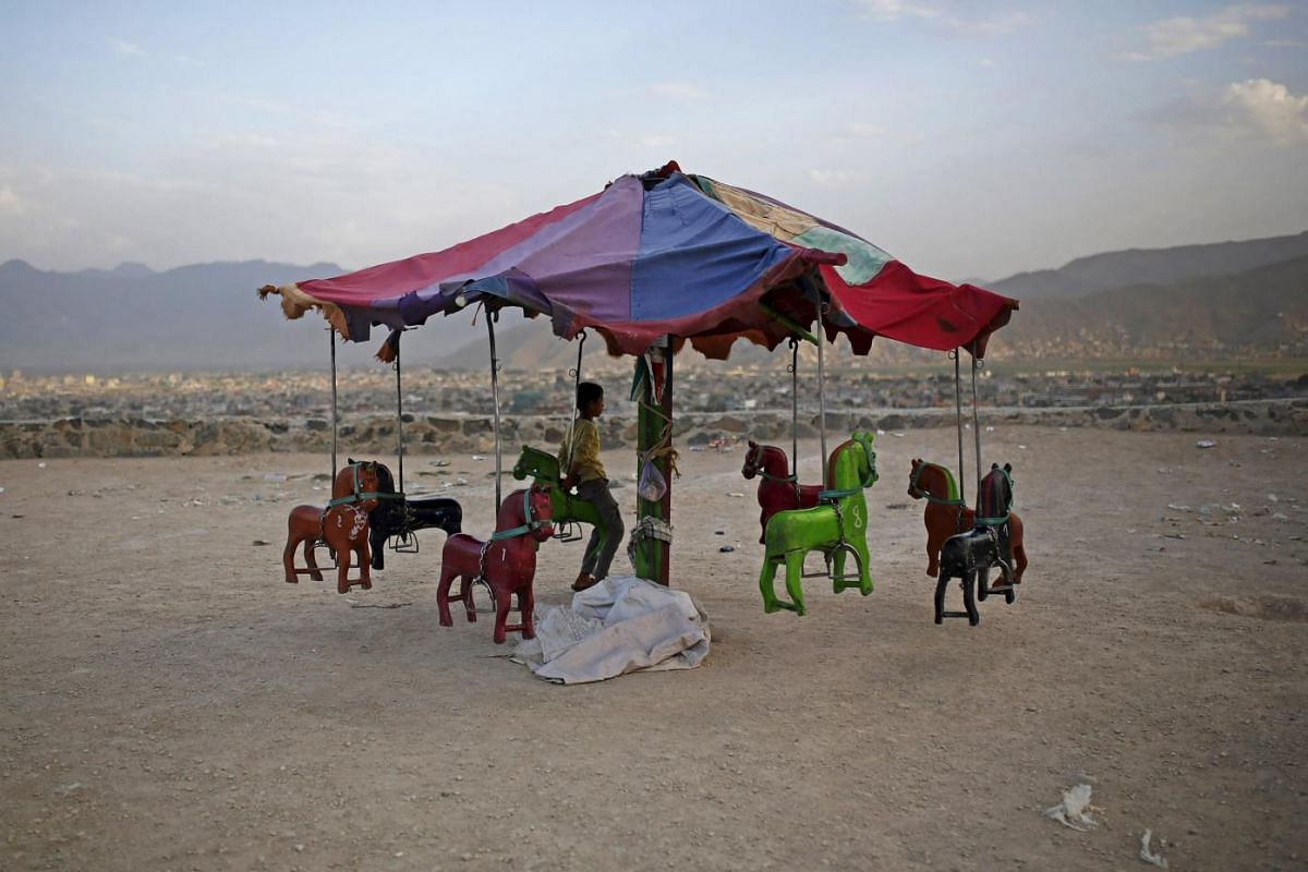 An Afghan boy sits on a merry-go-round on a hill top in Kabul.