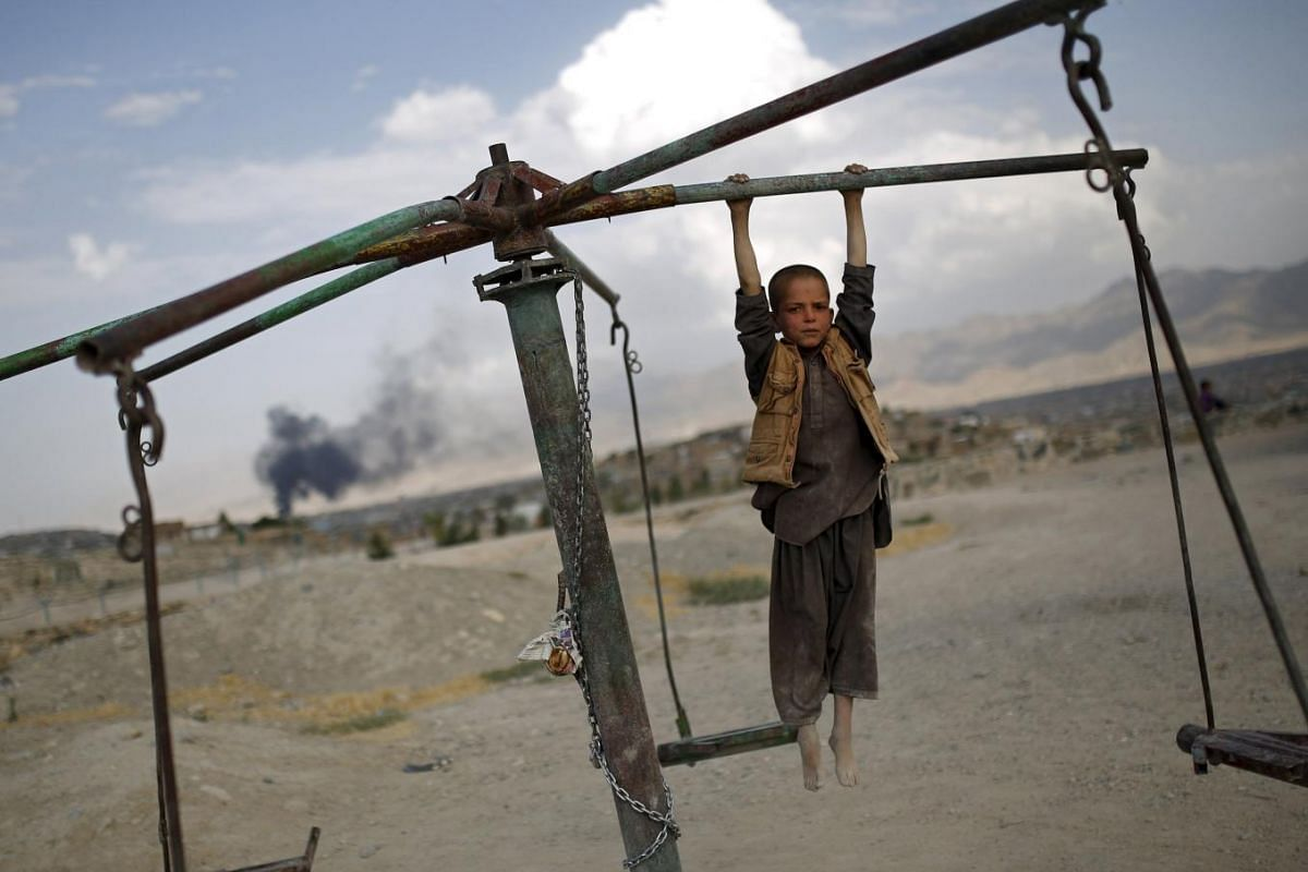 An Afghan boy plays on a merry-go-round on a hill top in Kabul.