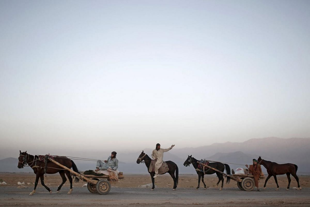 Labourers ride on their horse carts as they head to work on the outskirts of Kabul.