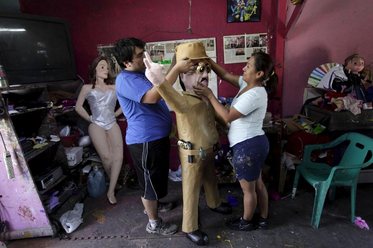 """Workers attach a hat to a pinata depicting the drug lord Joaquin """"El Chapo"""" Guzman at a workshop in Reynosa."""