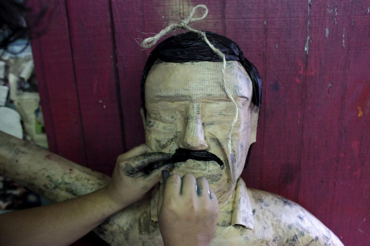 """Face time: A worker puts a mustache on to a pinata depicting the drug lord Joaquin """"El Chapo"""" Guzman."""