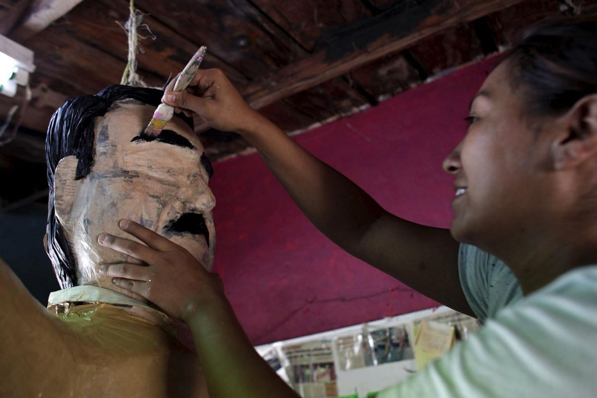 """First impression: A worker paints an eyebrow on a pinata depicting drug lord Joaquin """"El Chapo"""" Guzman."""
