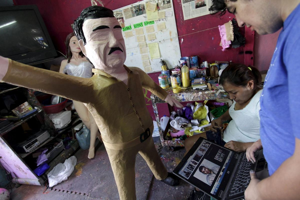 """Double check: Workers refer to images on a laptop in front a pinata depicting drug lord Joaquin """"El Chapo"""" Guzman."""