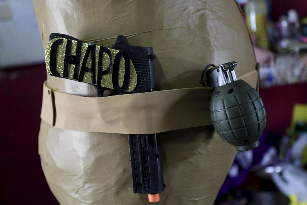 """Power play: A toy gun with the word, """"Chapo"""" is seen next to a toy grenade attached to a pinata depicting the drug lord Joaquin """"El Chapo"""" Guzman."""