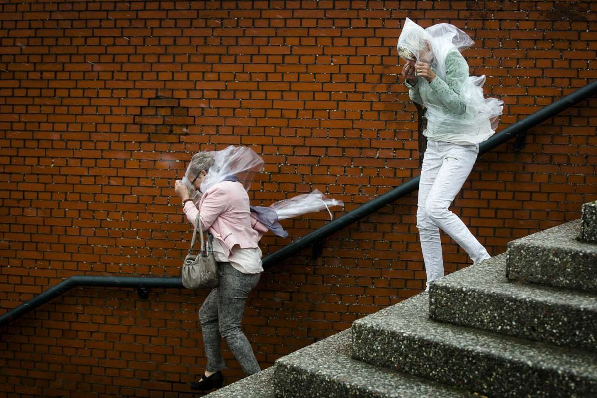 Pedestrians struggle with the wind near the coast in Scheveningen, The Netherlands, on July 27, 2015. A heavy storm is forecast in the area.