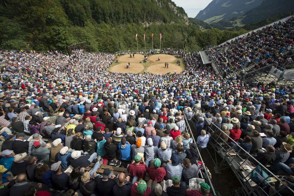Spectators at the wrestling arena during the Swiss Wrestling contest Schwingen, on the Bruenig Pass, Switzlerland, on July 26, 2015.