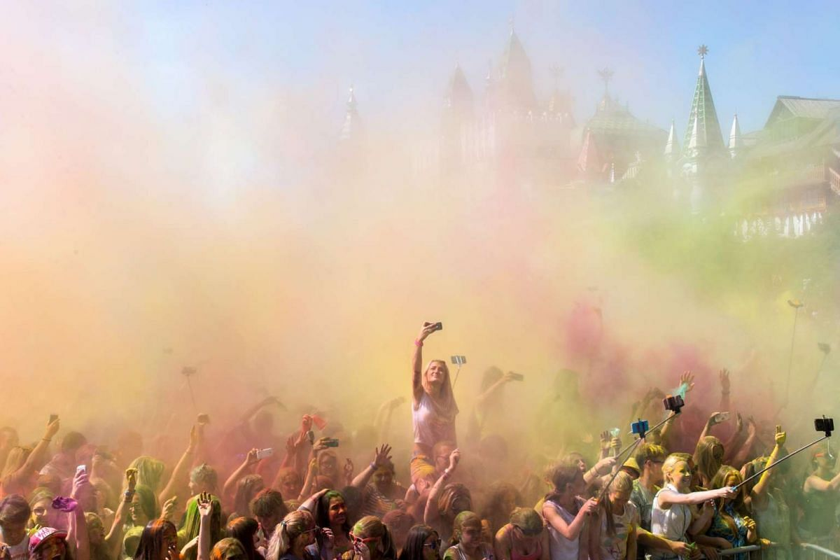 People throw coloured powder during the Holi Festival of Colours in Moscow on July 26, 2015.