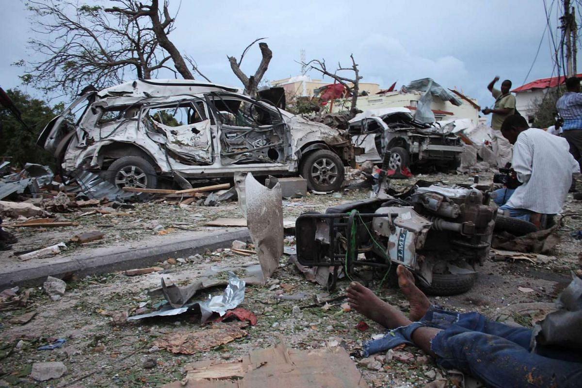A body lies in the rubble next to damaged cars near the Jazeera Palace hotel following a suicide attack in Mogadishu on July 26, 2015. Somalia's Shebab insurgents killed at least six people when they detonated a huge car bomb at a heavily guarded hot
