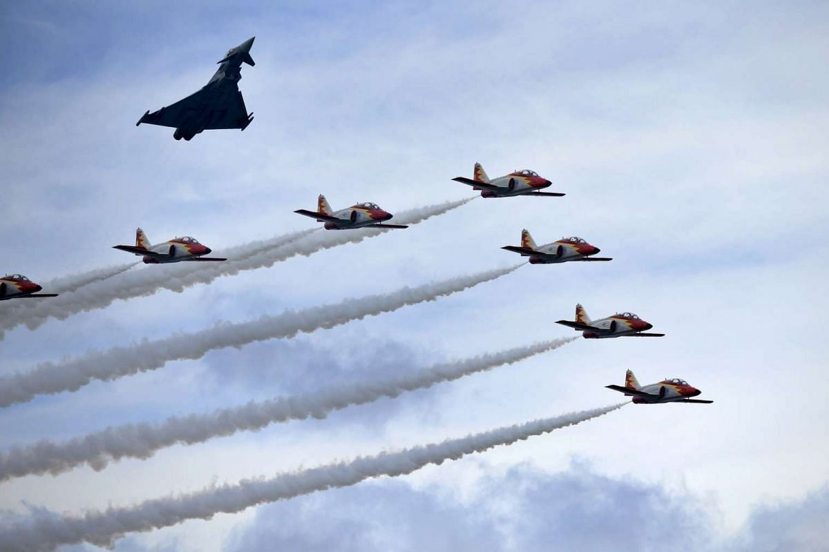 One Eurofighter and some C-101 Aviojets from the Spanish Air Force aerobatic group Patrulla Aguila fly over San Lorenzo beach during an aerial exhibition in Gijon, northern Spain, on July 26, 2015.