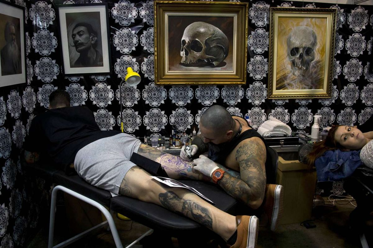 A Brazilian tattoo artist works on a man's leg during the Sao Paulo Tattoo Week 2015 in Sao Paulo, Brazil, on July 26, 2015.