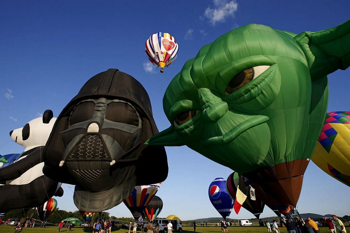 Hot air balloons shaped as Star Wars characters Darth Vader (left) and Yoda (right) are inflated at sunrise on Day 1 of the 2015 New Jersey Festival of Ballooning in Readington, New Jersey, on July 24, 2015.