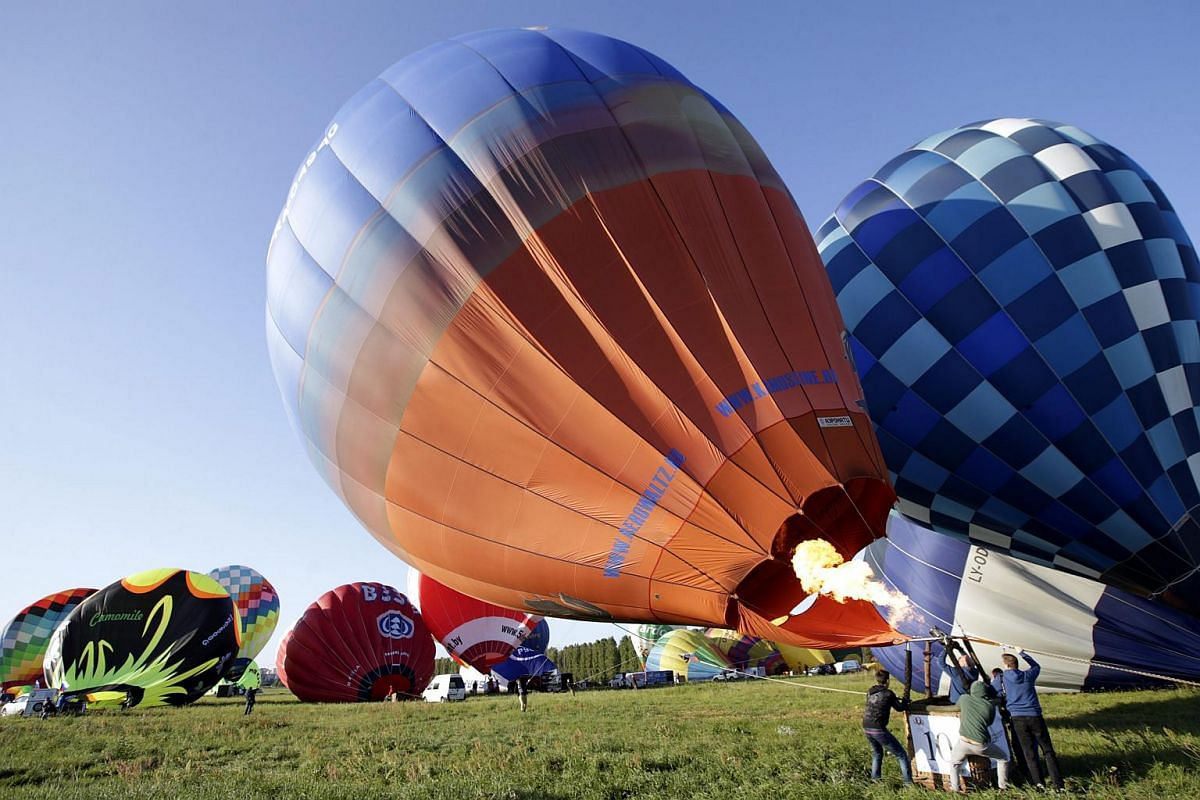 Aeronauts inflating hot air balloon before the start of flight during the Second International Aeronautics Championship 70 Years Of Peaceful Sky on the outskirts of Minsk, Belarus, on July 18, 2015.