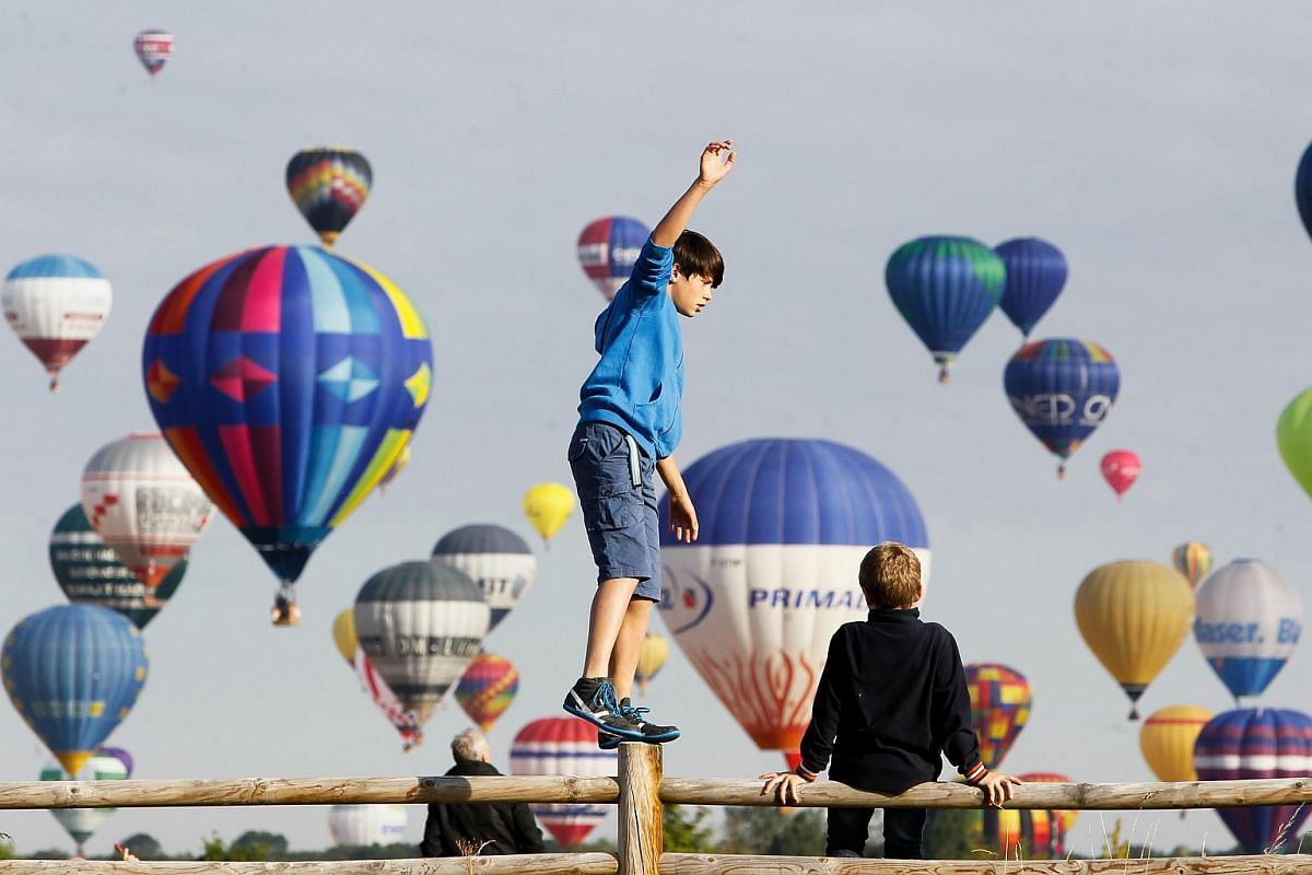Boys playing on a gate as hot air balloons fly over the Chambley-Bussieres air base during the international Lorraine Mondial Air Ballons festival, in Chambley-Bussieres, eastern France, on July 26, 2015.