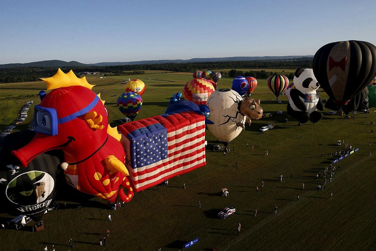 Hot air balloons in many shapes seen from a flying balloon just after sunrise on Day 1 of the 2015 New Jersey Festival of Ballooning in Readington, New Jersey, on July 24, 2015.