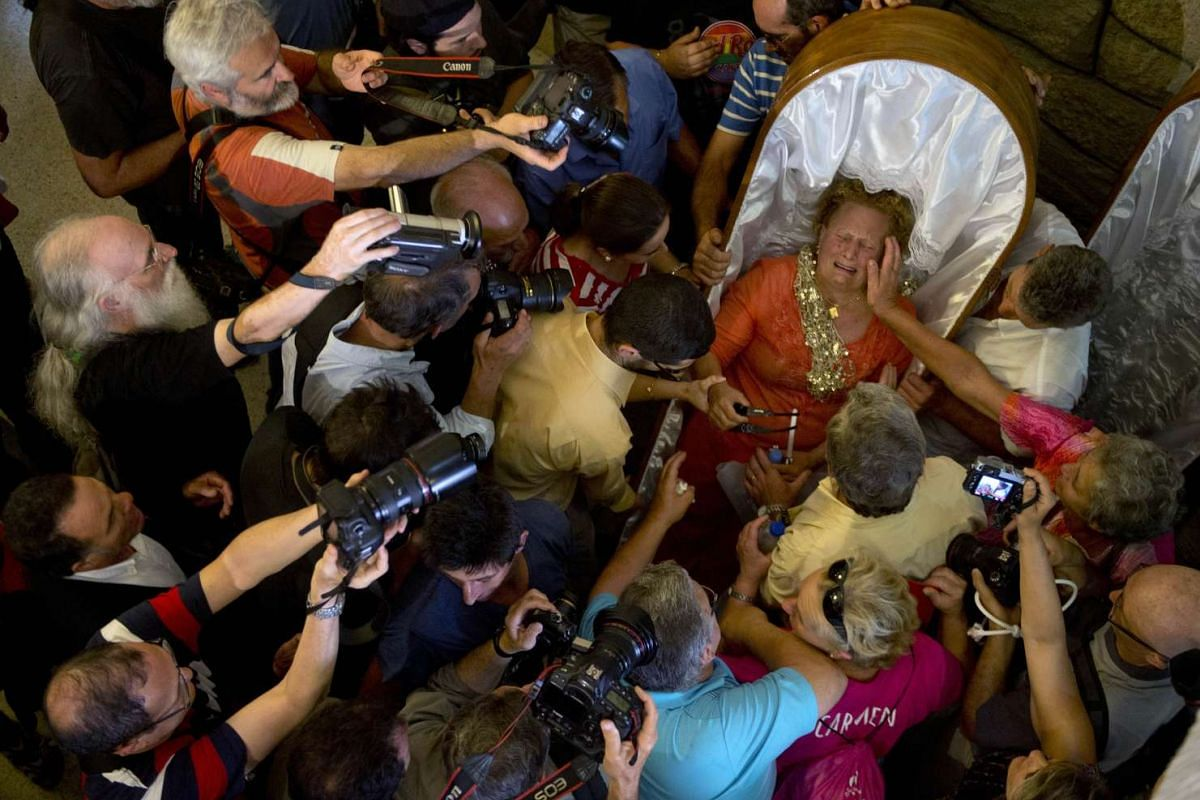"""A woman, mobbed by the press, is comforted inside the church after finishing the annual """"Procession of the Shrouds"""" to celebrate Santa Martha """"the saint of resurrection"""" in the village of Santa Marta de Ribarteme, northwestern Spain, on July 29, 2015"""