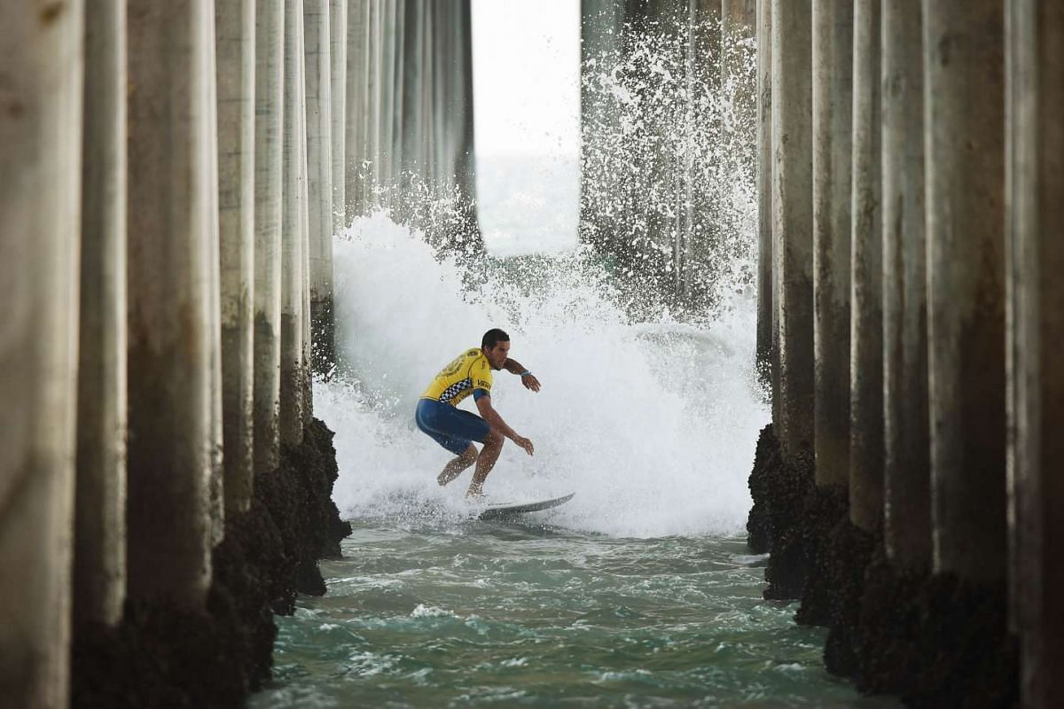 Professional surfer Ian Gouveia of Brazil 'Shoots the Pier' during his round two men's heat of the US Open of Surfing in Huntington Beach, California on July 29, 2015. The event celebrates it's 56th year beside the historic Huntington Pier which is c