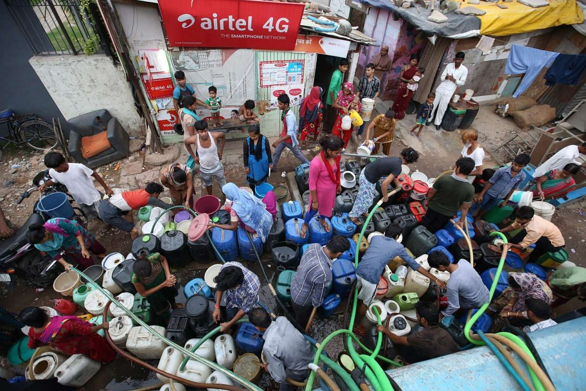 Indian people fill up canisters and containers with water from a tanker in New Delhi, India, July 30, 2015. According to a news report, around 20 per cent of Delhi's population do not have access to water supplied by pipes and are forced to rely on t