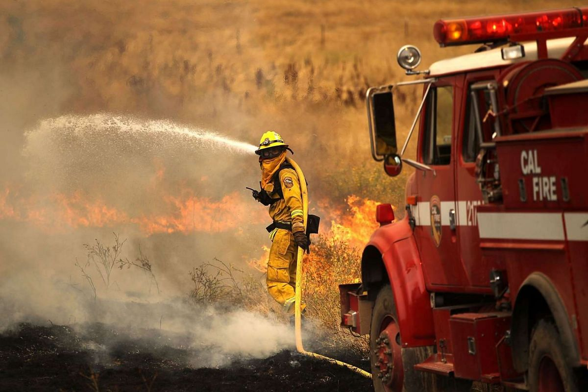 A firefighter uses a hose to put out a spot fire while battling the Rocky Fire on July 30, 2015 in Lower Lake, California.