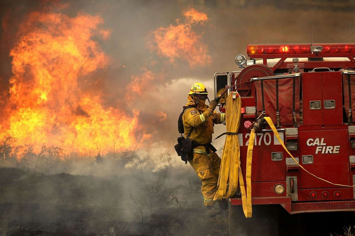 A firefighter rides on the side of a fire engine while battling the Rocky Fire on July 30, 2015 in Lower Lake, California.
