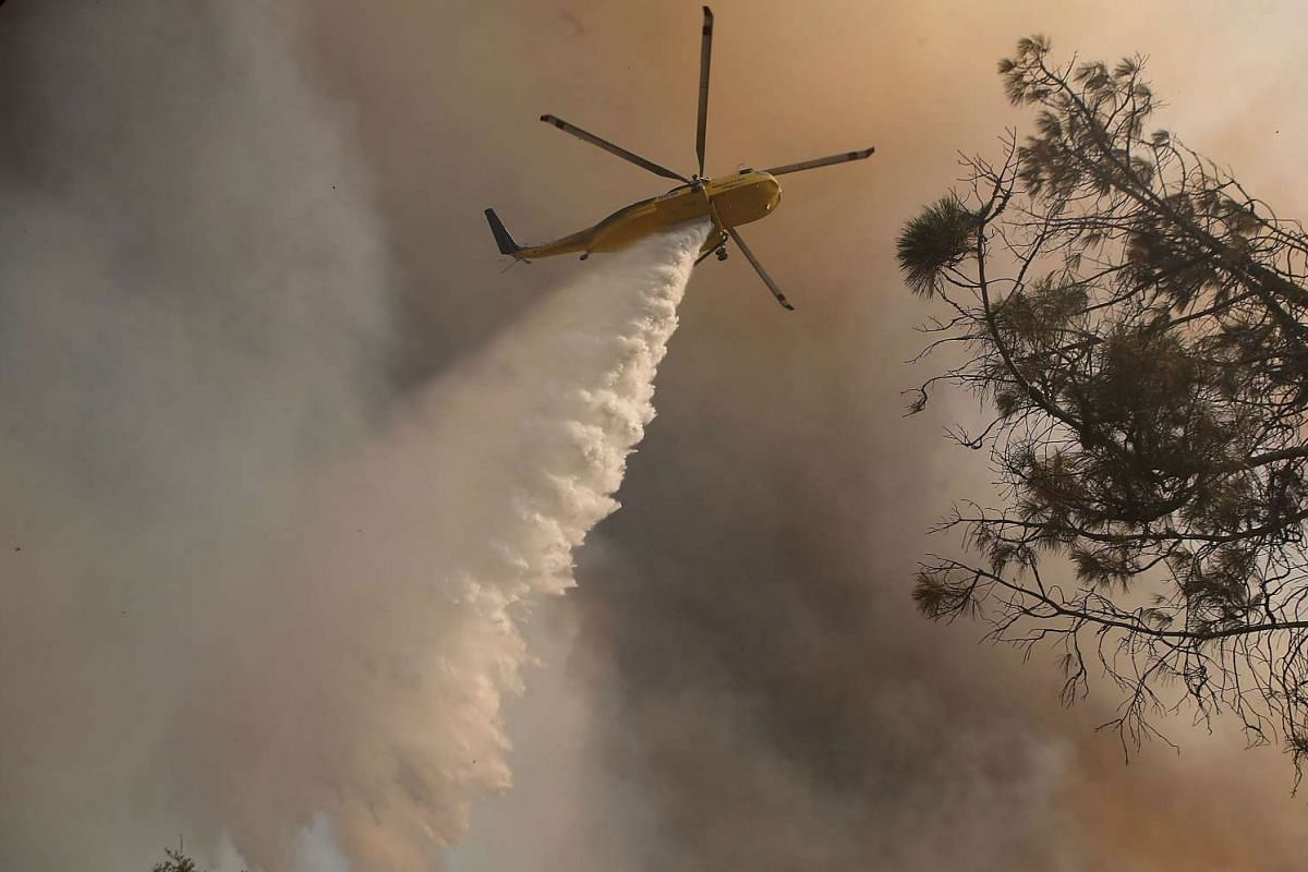 A firefighting helicopter drops water on spot fires while battling the Rocky Fire on July 30, 2015 in Lower Lake, California.