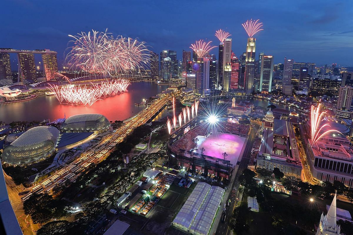An aerial view of fireworks going off simultaneously at different locations around the Marina Bay area.