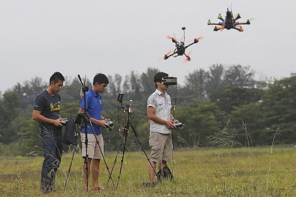 Drone racers (from left) Xu Zhuohua, Wong Wen Jie and Garry Huang get their speed fix in an open field and can view the landscape from their drones' perspective on a mounted monitor (below).