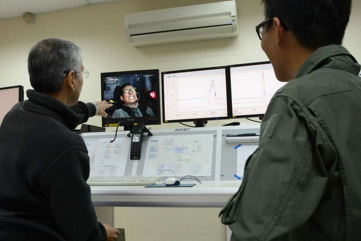 Dr Sanjiv Sharma (left), a Senior Aerospace Physiology Instructor, and Straits Times photojournalist Alphonsus Chern review a recent session in the Human Training Centrifuge at the ST Healthcare Aeromedical Centre.