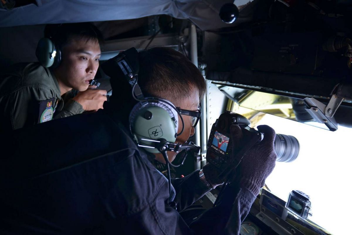 Straits Times photojournalist Alphonsus Chern (centre) photographs the RSAF Black Knights from the boom operator's position in a KC-135R Stratotanker.