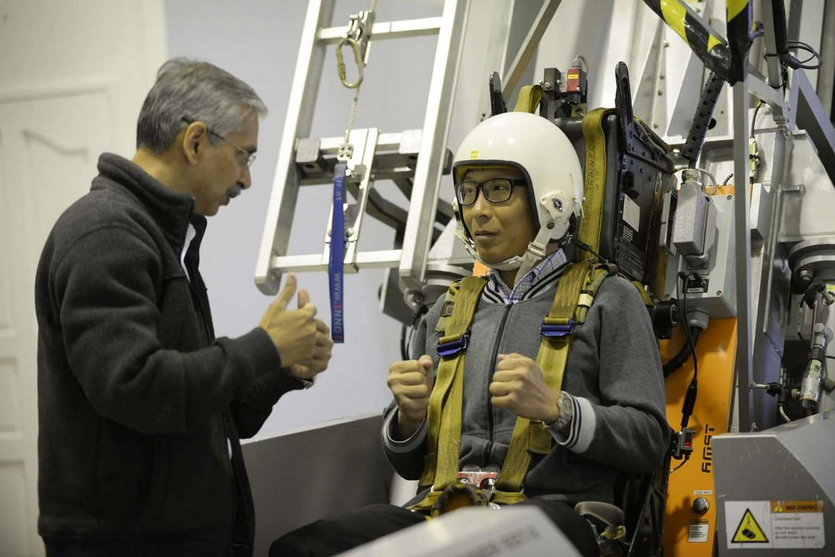 Dr Sanjiv Sharma (left), a Senior Aerospace Physiology Instructor, goes through the Ejection Seat Trainer procedure with Straits Times photojournalist Alphonsus Chern (left) at the ST Healthcare Aeromedical Centre.