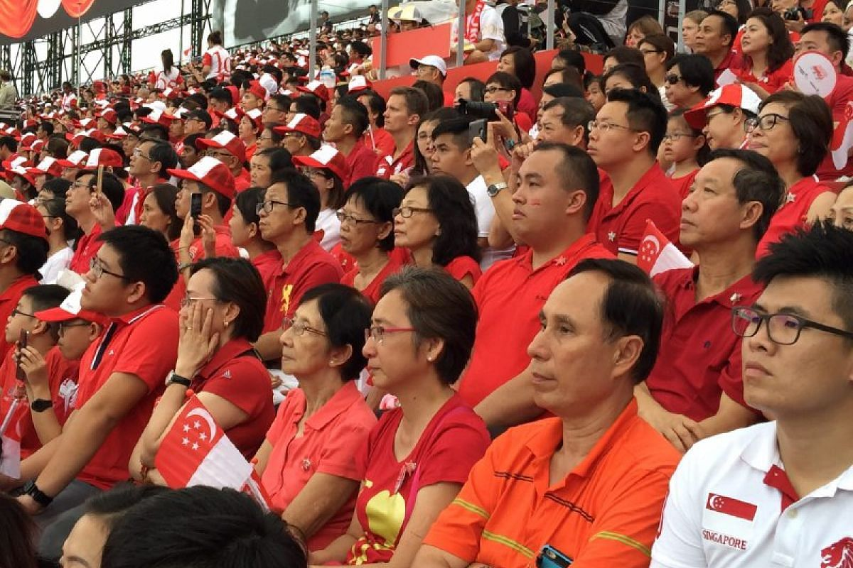 The audience watch a tribute video to the late founding prime minister Lee Kuan Yew.