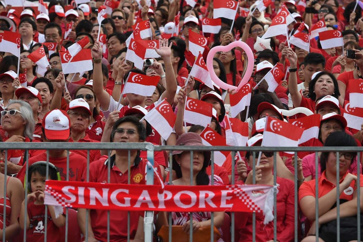 People wave national flags during Singapore's 50th National day anniversary celebration at the Padang in Singapore on Aug 9, 2015.