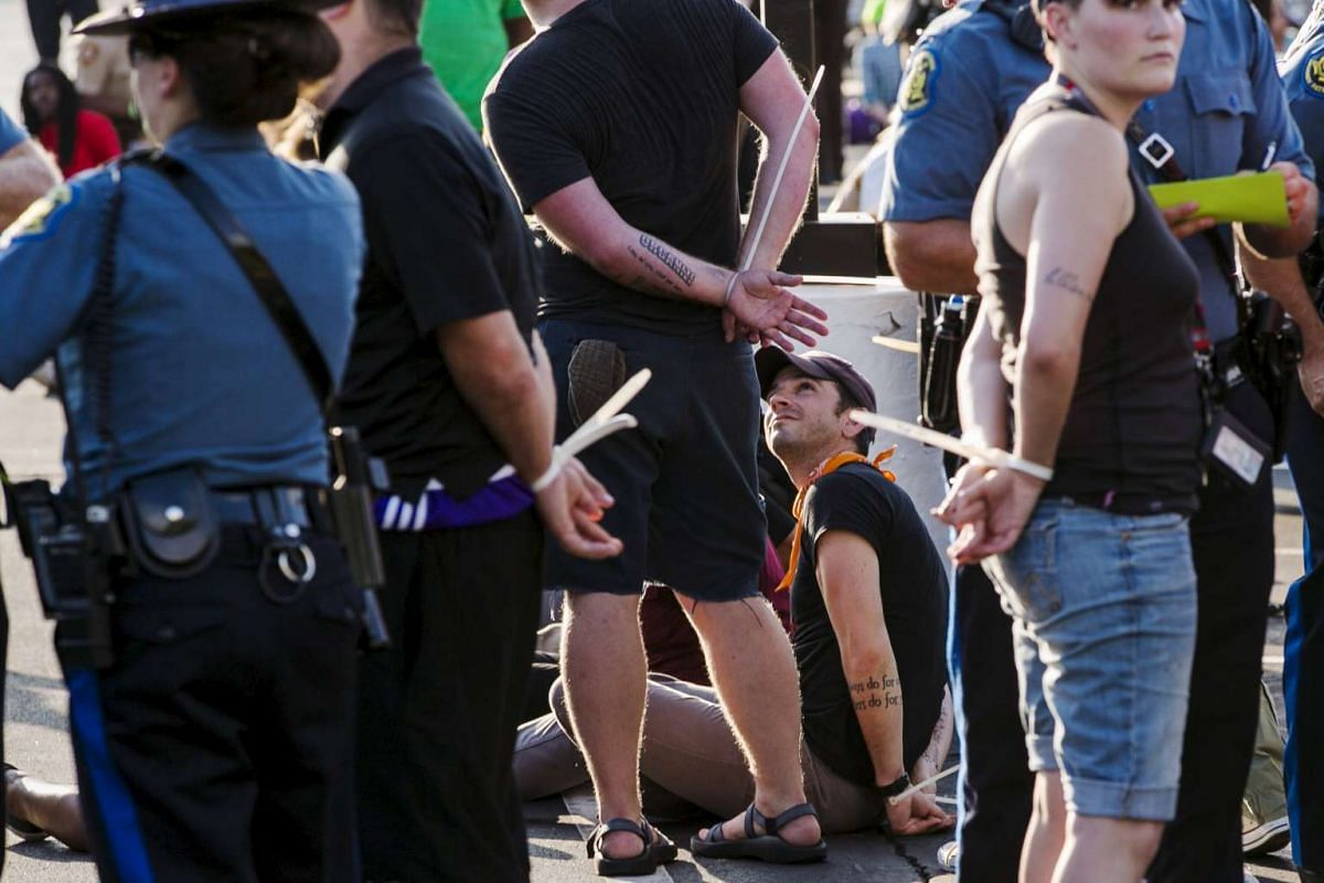 """Officers from the St Louis County Police Department and the Missouri Highway Patrol process demonstrators from the """"Black Lives Matter"""" movement that had been arrested for protesting on Interstate 70 in Earth City, Missouri, August 10, 2015."""