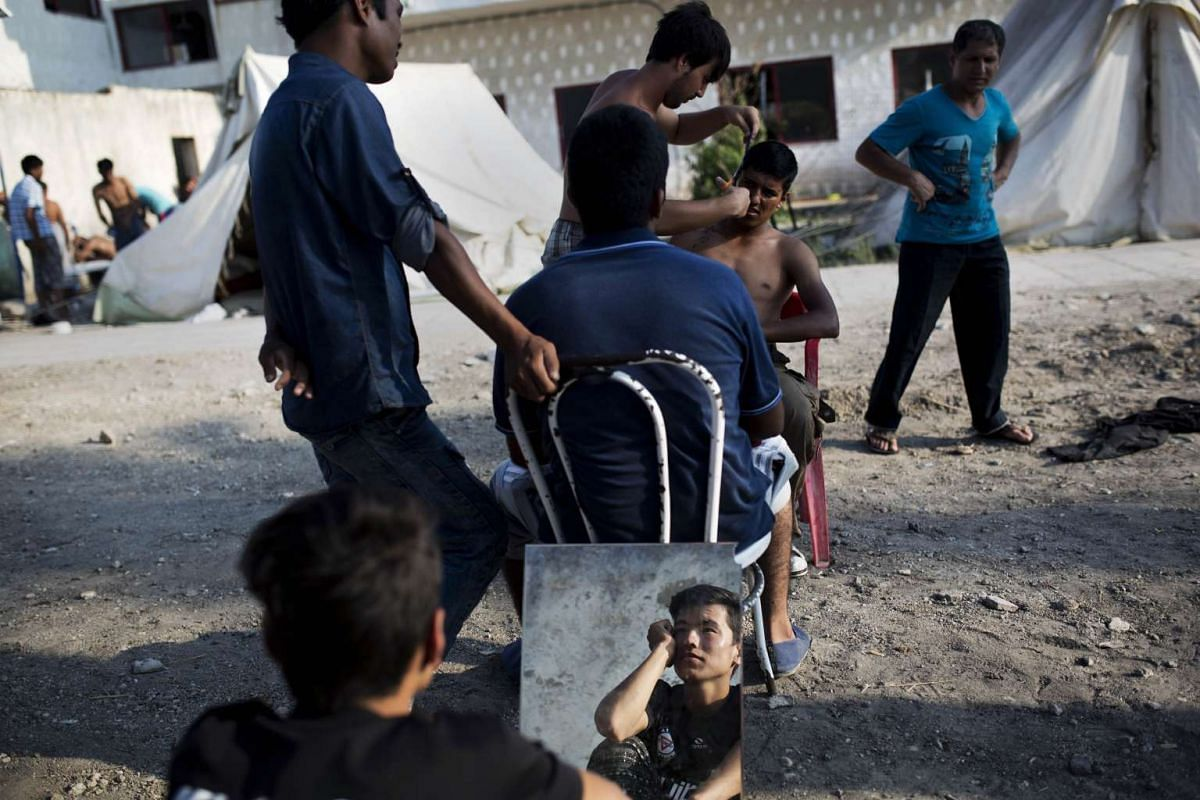 An Afghan migrant is reflected on a mirror as a man gets a hair cut next to a deserted hotel where hundreds of migrants have found temporary shelter, on the Greek island Kos on August 10, 2015.