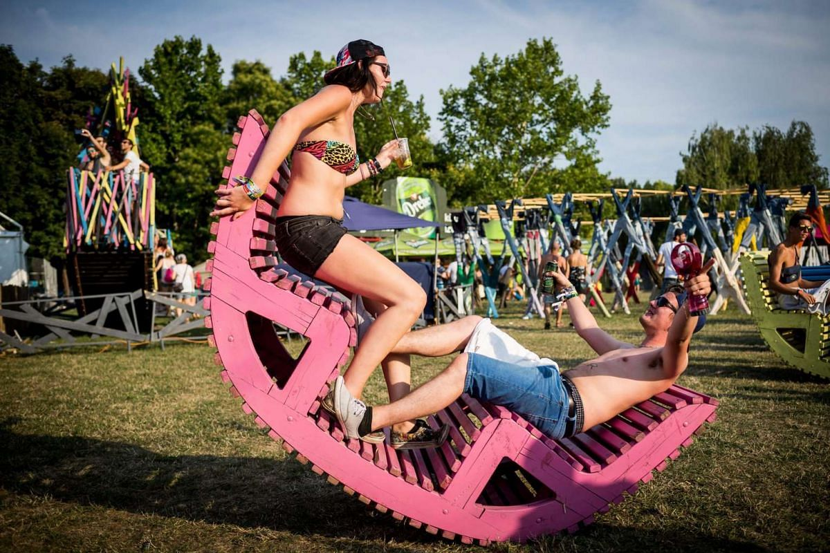 A couple enjoys a rocking chair on Shipyard Island, the venue of the 23rd Sziget (Island) Festival in Budapest, Hungary, 10 August 2015, during the opening day of the festival.