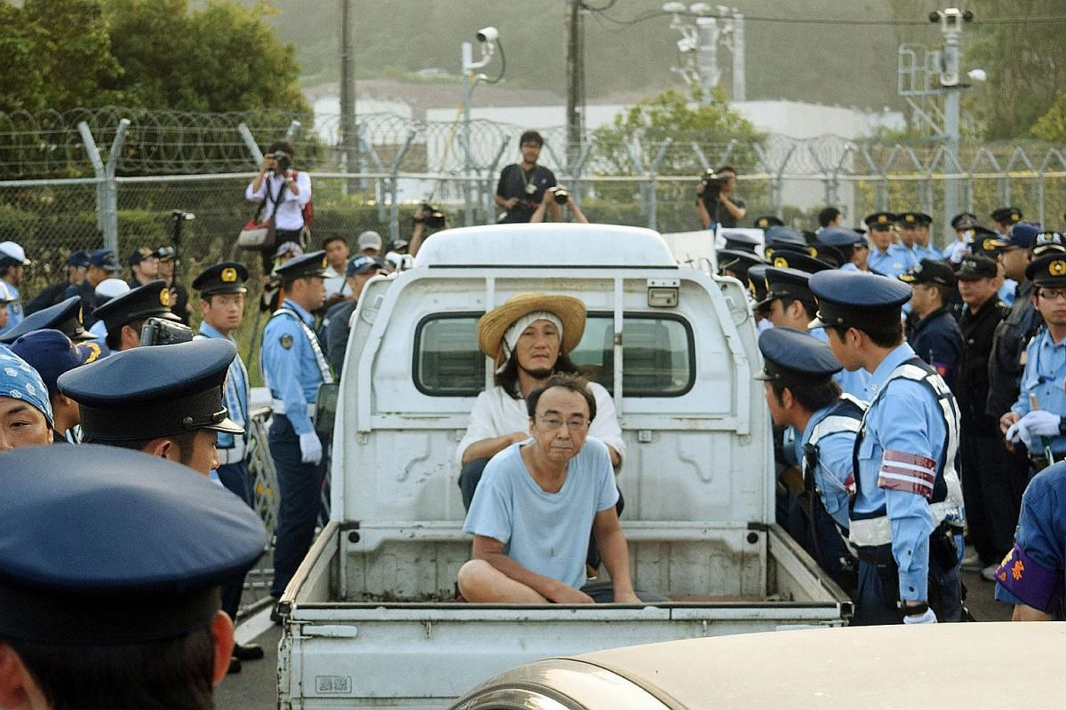 People sit in the flatbed of a truck as they stage a rally against the restarting of the nuclear reactor outside the gates of the Kyushu Electric Power Sendai nuclear power plant in Japan on Aug 11, 2015.
