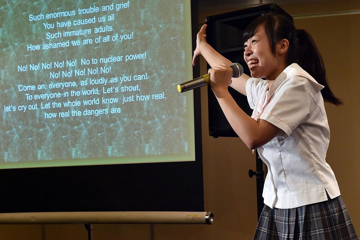 """Rina Nishino, a member of Japanese girls pop group """"Seifuku Kojo Iinkai"""", or The Uniform Improvement Committee, sings the song """"No No No to Nuclear Power"""" before the media at a press conference in Tokyo on July 28, 2015."""
