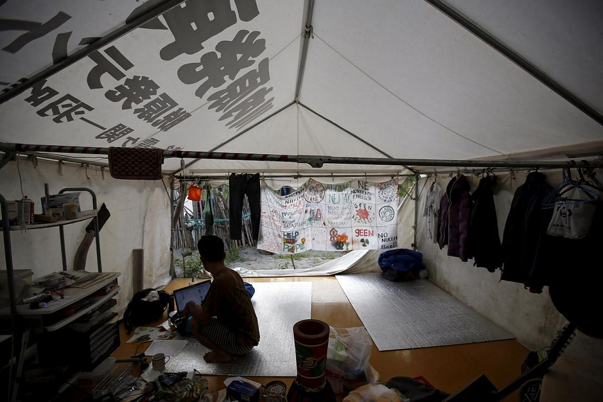 A person sits inside a tent at a protest campsite near Kyushu Electric Power's Sendai nuclear power station in Japan on Aug 7, 2015.