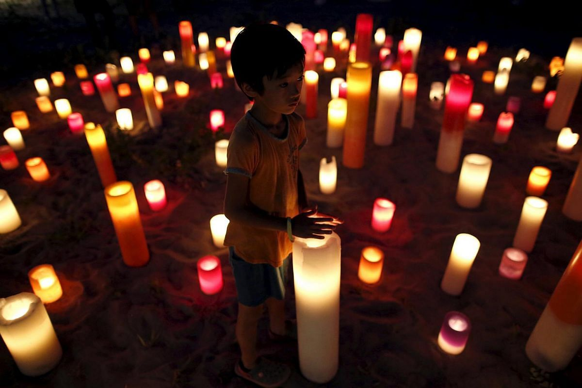 A boy stands near candles during an anti-nuclear event at the protesters' campsite near Kyushu Electric Power's Sendai nuclear power station in Japan on Aug 8, 2015.