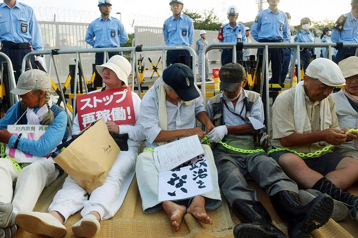 People stage a sit-in rally against the restarting of the nuclear reactor outside the gates of the Kyushu Electric Power Sendai nuclear power plant in Japan on Aug 11, 2015.