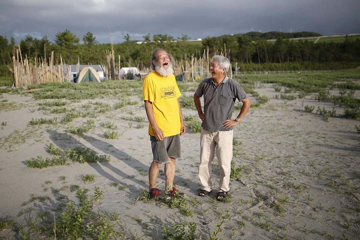 70-year-old Yoshiharu Ogawa (right) exchanges smiles with 66-year-old Mitsuro Sudo in front of their protesters' campsite on the sandy beach near Kyushu Electric Power's Sendai nuclear power station in Japan on July 8, 2015.