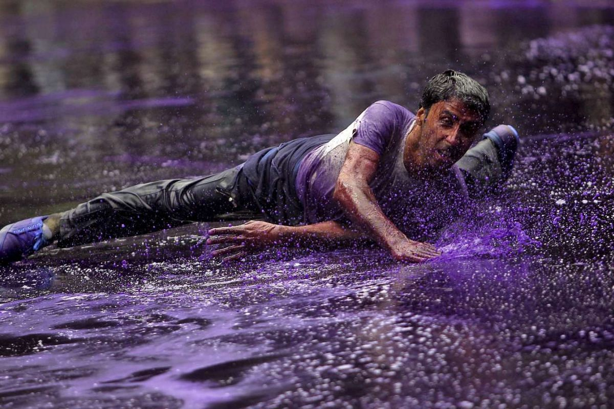 A government employee is hit by dyed water from a water cannon used by Indian police to disperse protesters during a demonstration in Srinagar, August 10, 2015.