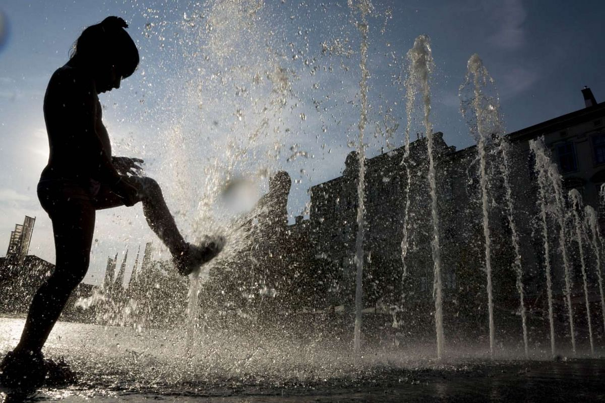 Children cooling down in a fountain outside of Columbus Shopping centre in Vienna on Aug 11, 2015, as a heatwave continues in the region where temperatures are reaching 38 deg C.