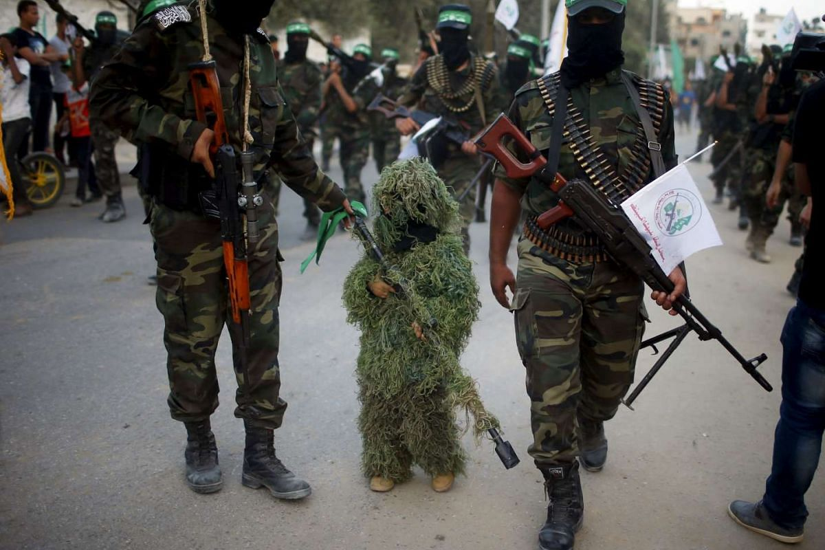 A masked Palestinian boy taking part with Hamas militates in an anti-Israel military parade in Beit Hanoun town in the northern Gaza Strip on Aug 11, 2015.