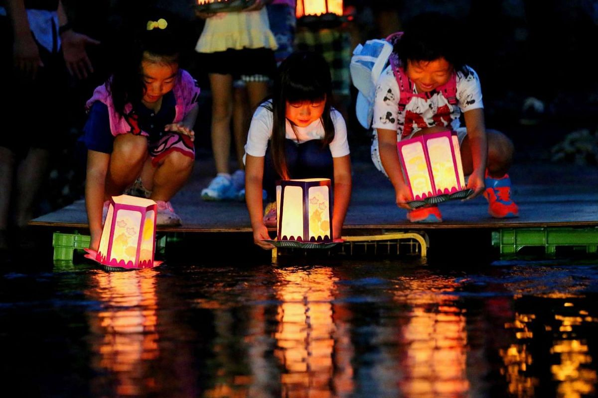Children releasing lanterns in the river to offer prayers for the victims of Japan Airlines (JAL) jumbo jet crash at Ueno village in Gunma prefecture, north-west of Tokyo on Aug 11, 2015, the eve of the 30th anniversary of the accident.