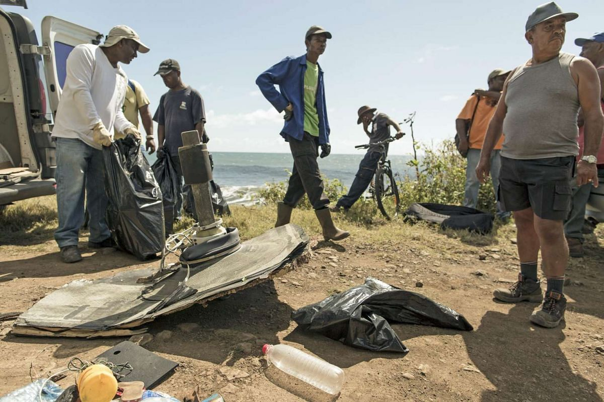 Volunteers gathering large debris found on the coast of Sainte Suzanne, Reunion Island, France, on Aug 11, 2015. The searches continue on La Reunion since a first debris of the MH370 was found.