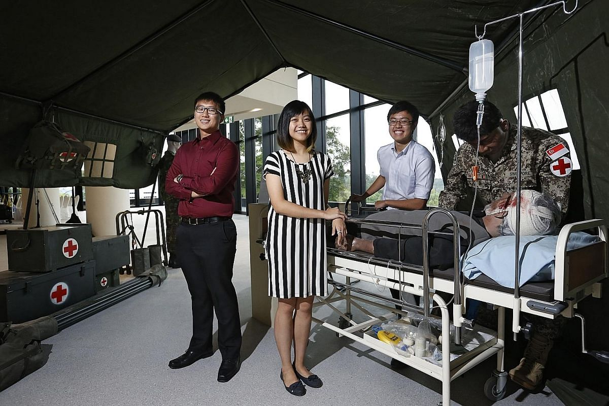 Second-year students (from left) Berwyn Tan, 19, Candice Loh, 19, and Shawn Tan, 20, at the opening of the Humanity in Medicine exhibition at NTU Lee Kong Chian School of Medicine's Experimental Medicine Building yesterday.