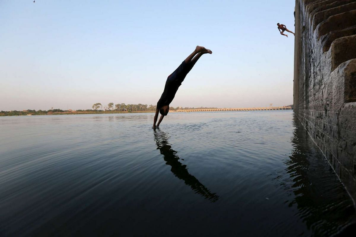 A boy jumping into the river Nile in hot weather on the outskirts of Cairo, Egypt, on Aug 12.