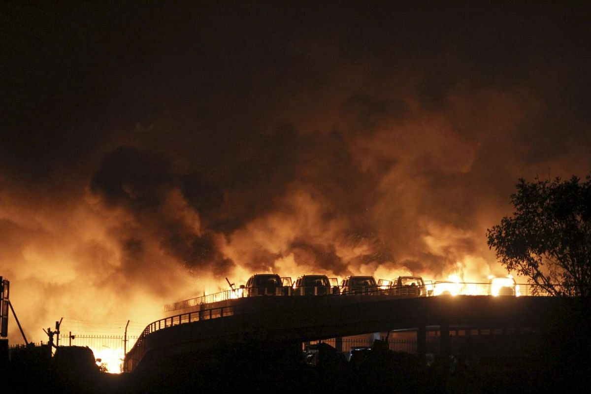Vehicles burning after blasts at the Binhai new district in Tianjin on Aug 13.
